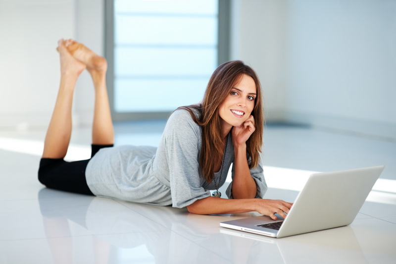 Portrait of beautiful young woman lying on floor with a laptop - Indoor
